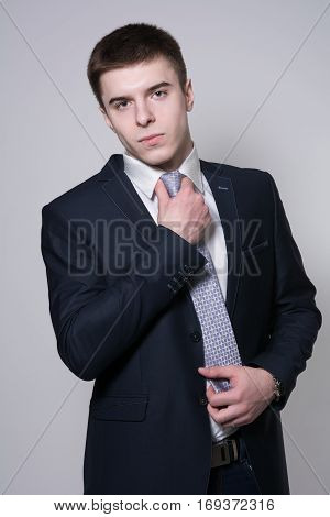 Portrait Of A Business Man Adjusting His Tie