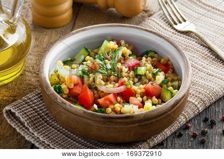 Couscous with tomatoes cucumber and onion in a bowl for healthy breakfast. Traditional Israeli food Ptitim with vegetables. Moroccan cuisine meal.
