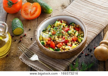 Couscous with tomatoes cucumber and onion in a bowl for healthy breakfast. Traditional Israeli food Ptitim with vegetables. Moroccan cuisine meal. Top view.
