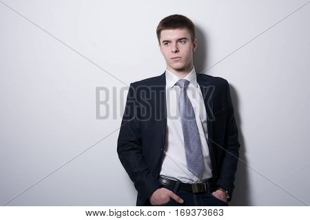 Successful Businessman With Hands In Pockets Looking Away.