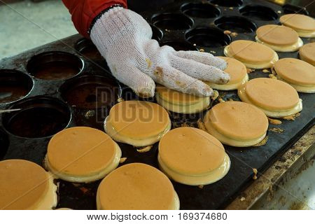 Japanese pancake on retro metal hot plate with flavouring show by hand.