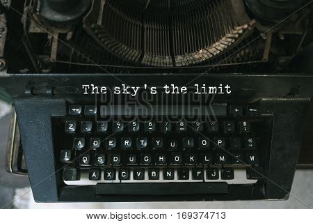 Typewriter with white paper page on wooden table. sample text The sky's the limit.