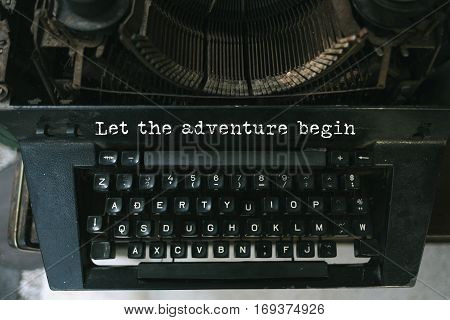 Typewriter with white paper page on wooden table. sample text Let the adventure begin.
