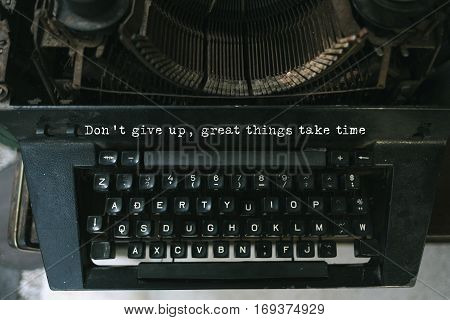Typewriter with white paper page on wooden table. sample text Don't give up. Great things take time.