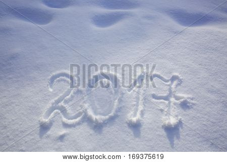 New years date 2017 written in fresh powder snow. New Year 2017 greeting, 2017 numbers written on snow field, greeting card background.