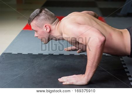 man push up chest exercise and gritty serious facial expression inside gym.