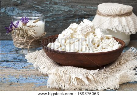 Cottage cheese in a clay plate, glass with milk on a wooden background. Country style
