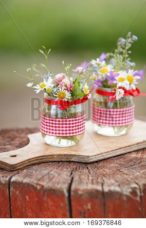 Beautiful summer wild flowers in a nice glass jar on a wooden background. Summer bouquet. Bunch of flowers. Summer time. Present.