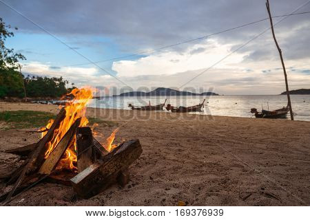 Fire burning on the beach on a background of sea sunset. Thai fishing boat. longtail boat. Thailand Phuket.