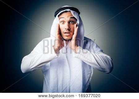 studio shot of young man wearing traditional arabic clothing