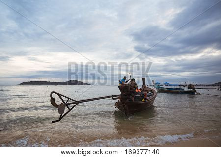THAILAND PHUKET ASIA - DECEMBER 21 2016: Thai fishermen are sent to the production of fish. Motor boat Longtail people on board.