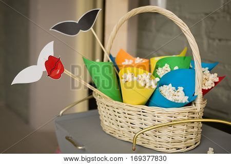 Pop corn in colorful paper cones in a white basket. Preparations for a party.accessories for a fun holiday of paper lips mustaches.