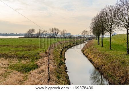 Floodplains of a wide Dutch river on a cloudy day in the winter season. In the foreground the mirror smooth reflecting water surface of s mall stream.