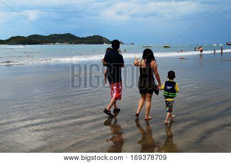 IXTAPA,MEXICO-Dec.4,2016: Family strolling on the beach at Playa Linda in Ixtapa, Guerrero,Mexico.