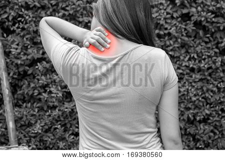 Young woman nape or joint pain at outdoor in black and white concept