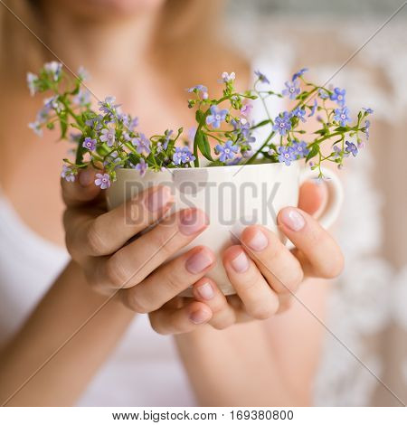 Young girl in a white tank holding a dotted cup with forget-me-not. Flowers in a mug. Hands with flowers. Smiling woman with spring flowers. Tenderness