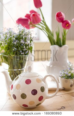 Teapot with dots and vases with beautiful spring flowers on the wooden table. Decoration for home interior. Forget-me-not and tulips in vases. Flowers from the garden.Tea time and table setting.