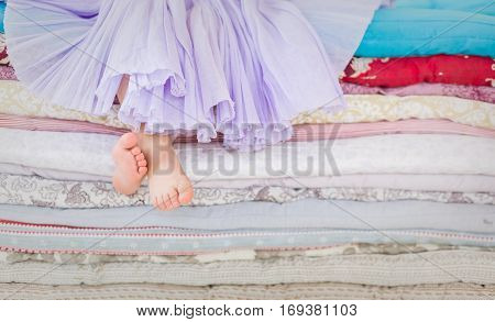 The fairy tale the princess on a pea. Little girl in lilac tatu skirt sitting on the high bed. Bare foot if the girl. Legs of a little girl sitting on a pile of colorful mattresses.