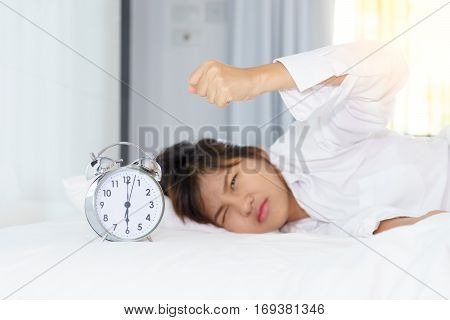 Angry young woman looking at alarm clock with clench one's hand in the morning. early wake up.