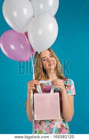 Sweet Girl With Baloons And Little Prersents Bag In The Hands On The Blue Background