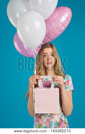Sweet Nice Girl With Baloons And Little Prersents Bag In The Hands On The Blue Background. Spring Mo