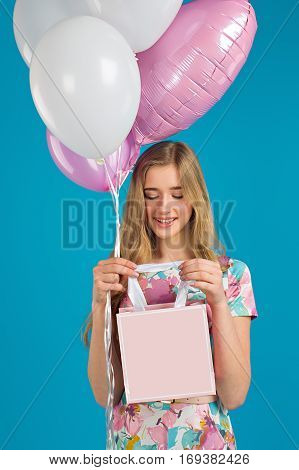 Sweet Girl With Baloons And Little Prersents Bag In The Hands On The Blue Background.