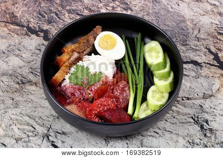 Ready served of Thai food Jasmine rice with Chinese sausagered herb pork crispy streaky pork and boiled egg topped red sweet sauce served with cucumber and shallot call Khao Moo Daeng in Thai.