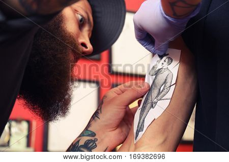Tattoo master in studio attaching sketch to male arm, close up view