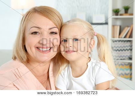 Cute happy girl with grandmother at home