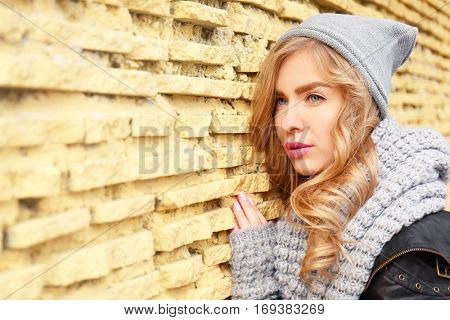 Young beautiful woman standing on yellow brick wall background