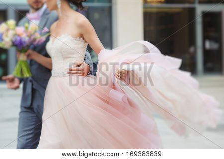 Luxury bride holding a flying pink wedding dress and walking. Beautiful bride in a luxurious dress. Groom hugs bride walking on the street.