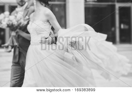 Luxury bride holding a flying pink wedding dress and walking. Beautiful bride in a luxurious dress. Groom hugs bride walking on the street. black and white photo