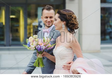 Happy bride and groom walking. Luxury bride holding a flying pink wedding dress and walking. Beautiful bride in a luxurious dress. Groom hugs bride walking on the street.