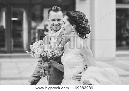 Happy bride and groom walking. Luxury bride holding a flying pink wedding dress and walking. Beautiful bride in a luxurious dress. Groom hugs bride walking on the street. black and white photo