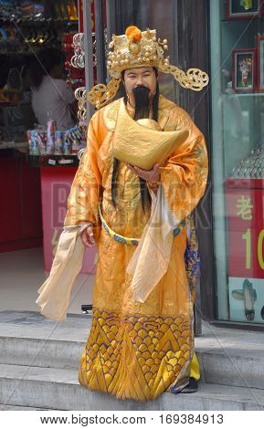 BEIJING, CHINA - JUN.24, 2012: Actor in Chinese traditional costume as the God of Wealth (Cai Shen) in Beijing, China. God of Wealth (Cai Shen) is invoked in Chinese New Year with Golden Sycee (Golden ingot) in his hand.