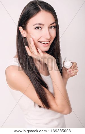 Applying cosmetic cream. A beautiful young woman applying face moisturizer. Scine care of the face and hands.