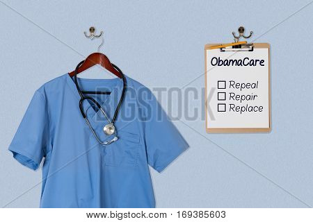 Blue medical scrubs uniform shirt hanging on a hanger with stethoscope with Obamacare options on clipboard
