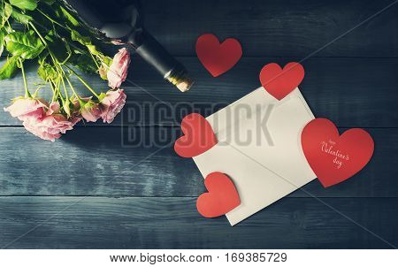 Valentine's Day card with a bouquet of roses and a bottle of wine. Old blue wooden background with copy space