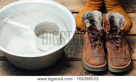 Feet wearing wool socks near winter fur boots and basin on the floor before footbath