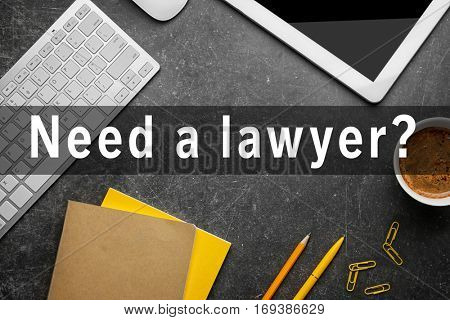 Office supplies on table. Text NEED A LAWYER? on background