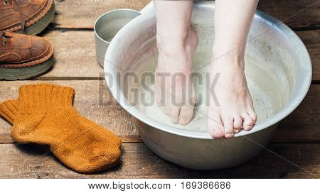Footbath closeup. Bare feet in basin with warm water,  boots and wool socks on the floor