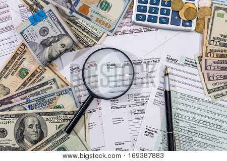 1040 Tax Form With Magnifying Glass Dollars, Pen And Calculator.