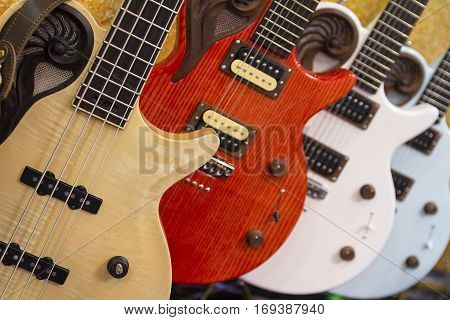 Many colorful electric guitars aligned in a store showroom body detail