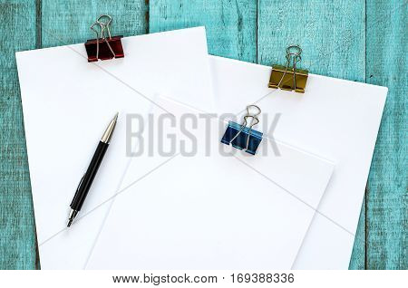 Blue Wooden Desk Table With Paper Reams And Pen.
