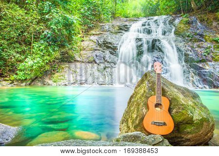 Ukulele on the rock inTropical waterfall in the forestTon Chong Fa in khao lak Phangnga South of Thailand