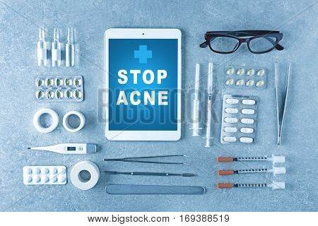 Dermatologist equipment on gray background. Text STOP ACNE on tablet screen