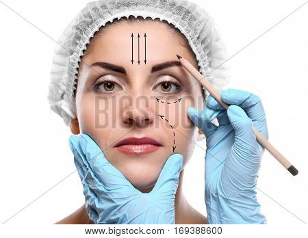 Plastic surgery concept. Doctor drawing marks on female face against white background