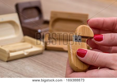 Woman holding ecological wooden a USB flash drive