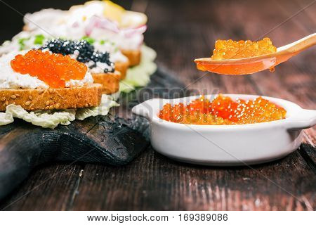 Toasts with farmer cheese and salmon roe top on rustic serving board