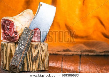 Meat chopper and pork leg on wood block over fire light background